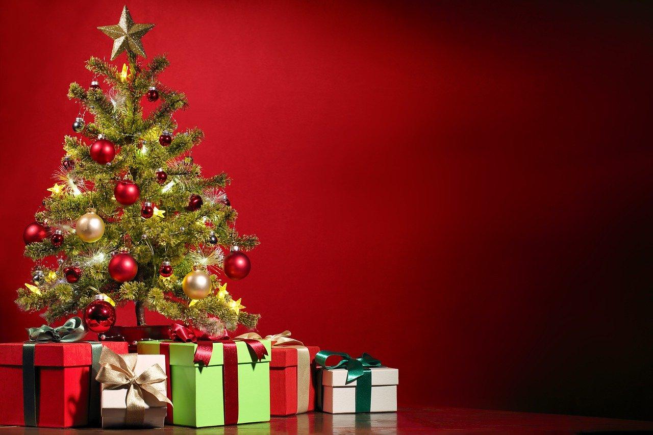 Weihnachtsbaum mit Geschenken vor roten Hintergrund